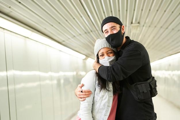 Молодые межрасовые пары обнимаются в коридоре подземного метро.