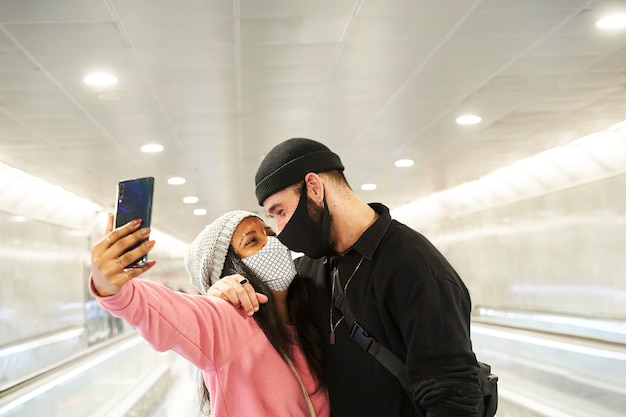 A young interracial couple of lovers wearing face masks and wool hats making a selfie in a subway or airport corridor.