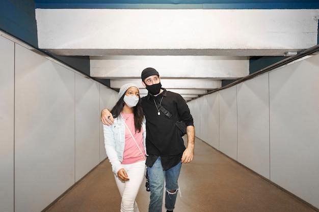 Молодые межрасовые пары влюбленных в коридоре метро.