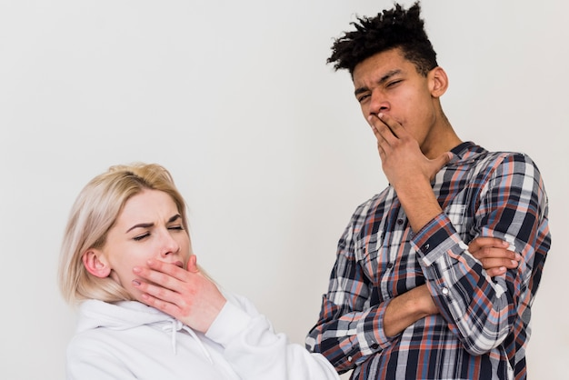 Young interracial couple standing against white wall yawning