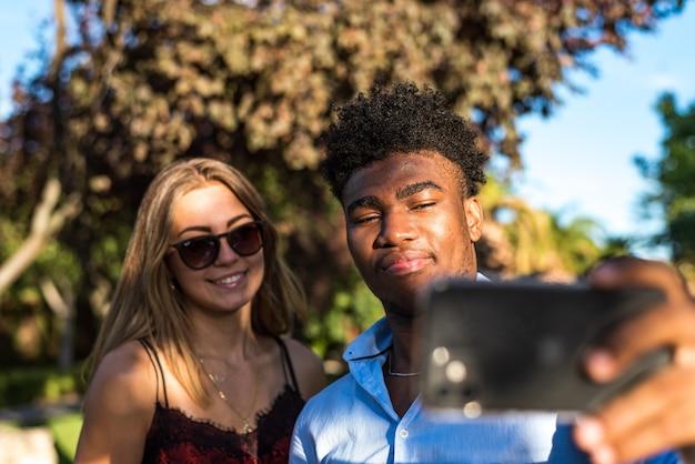 그들의 휴대 전화와 함께 공원에서 selfie를 복용 하는 젊은 인종 커플.