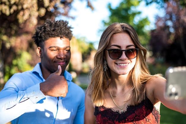 그들의 휴대 전화로 selfie를 복용 하는 젊은 인종 커플.