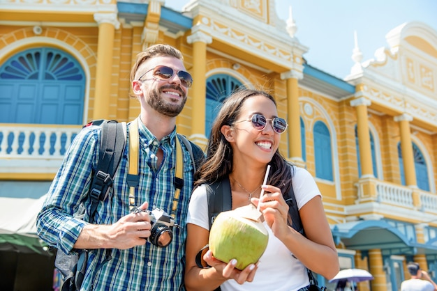 Young interracial couple tourist backpackers enjoying traveling in bangkok city thailand