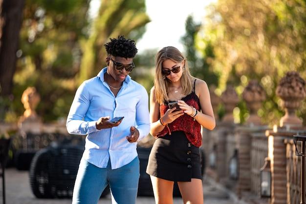 레스토랑 테라스에서 휴대전화를 사용하는 젊은 인종간 커플. 흑인 남성과 백인 소녀.
