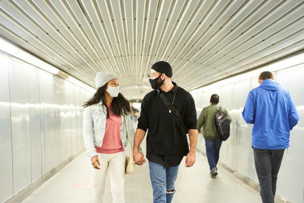 Young interracial couple walking hand in hand in an underground subway corridor.
