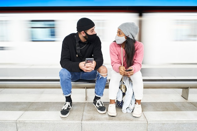 A young interracial couple with masks and wool hats sits on the subway platform talking