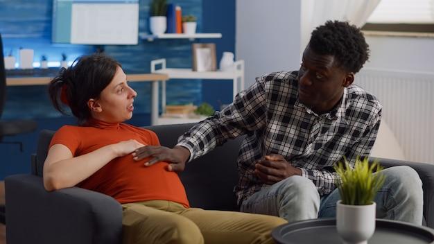 赤ちゃんについておしゃべり妊娠中の若い異人種間のカップル