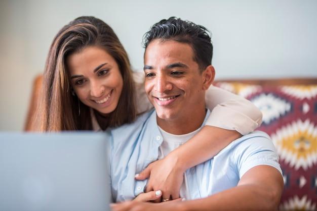 ラップトップと一緒に働く若い異人種間のカップル。インターネット接続を使用して一緒に家で人々のライフスタイル-男性と女性は無料で幸せなコンピュータとオンラインの現代的な仕事を楽しんでいます