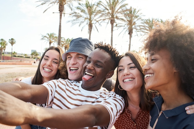 若い異人種間の友人は、一緒に自由な時間を楽しんでいる人々の写真グループを撮ります