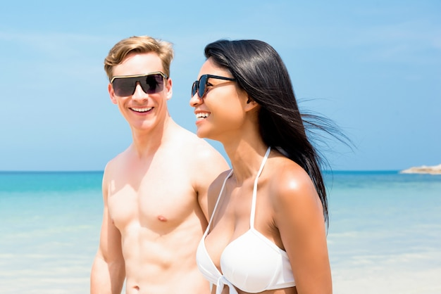 Young interracial tourist couple strolling along the beach