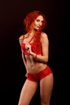 검은 배경에 란제리에 젊은 친밀한 빨간 머리 여자 아름다움 초상화.