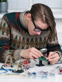 전자 부품을 시험하는 젊은 발명가.