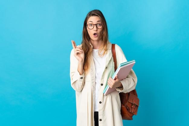 Молодая студентка из ирландии на изолированном фоне, намереваясь реализовать решение, подняв палец вверх