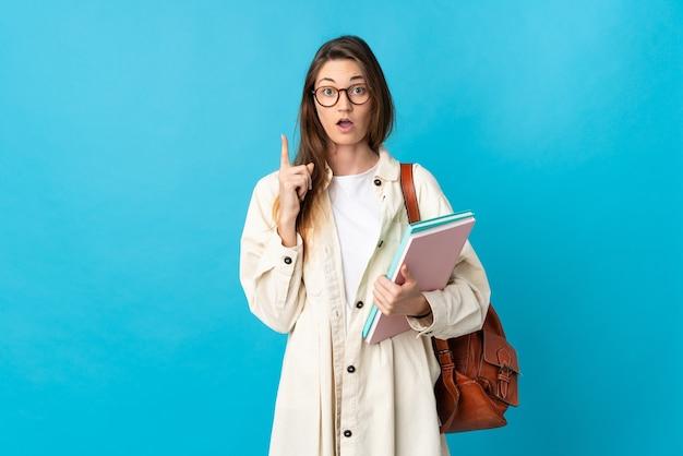 Молодая женщина студента ирландии над изолированной думая идеей указывая пальцем вверх