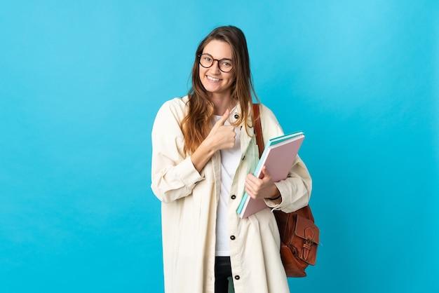 Молодая женщина-студент из ирландии над изолированной стеной показывает палец вверх