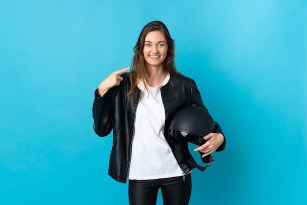 Молодая ирландская женщина, держащая мотоциклетный шлем, изолирована на синем фоне, показывая жест рукой вверх