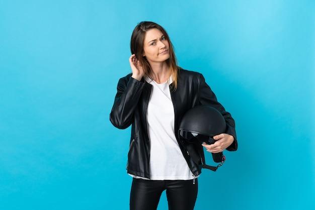Молодая ирландская женщина, держащая мотоциклетный шлем, изолирована на синем фоне и сомневается