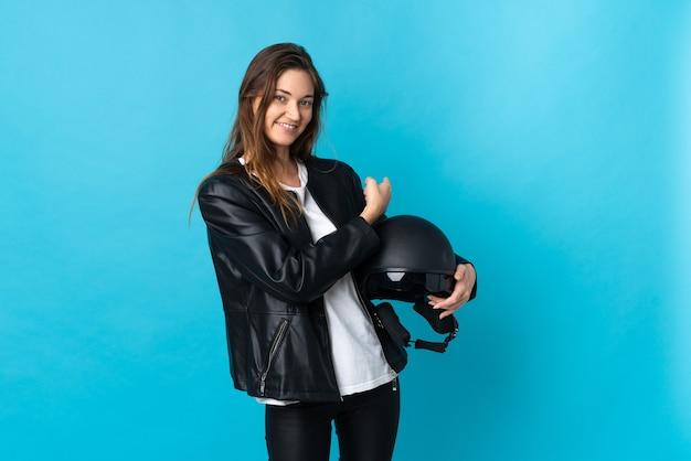 Молодая ирландская женщина, держащая мотоциклетный шлем, изолирована на синем фоне, указывая назад
