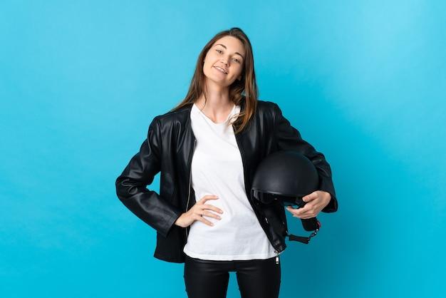 腰に腕と笑顔でポーズをとって青い背景で隔離のオートバイのヘルメットを保持している若いアイルランドの女性