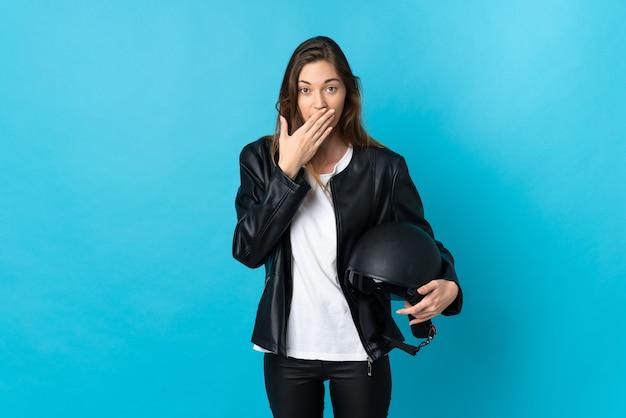 青い壁に分離されたオートバイのヘルメットを持って幸せで笑顔の若いアイルランドの女性が手で口を覆う