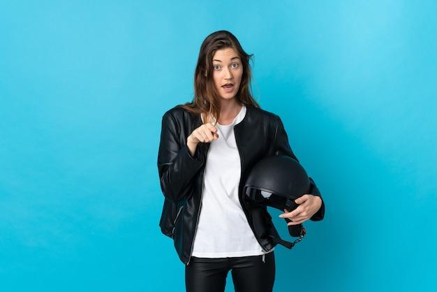 青い壁に分離されたオートバイのヘルメットを保持している若いアイルランドの女性は驚いて正面を指しています