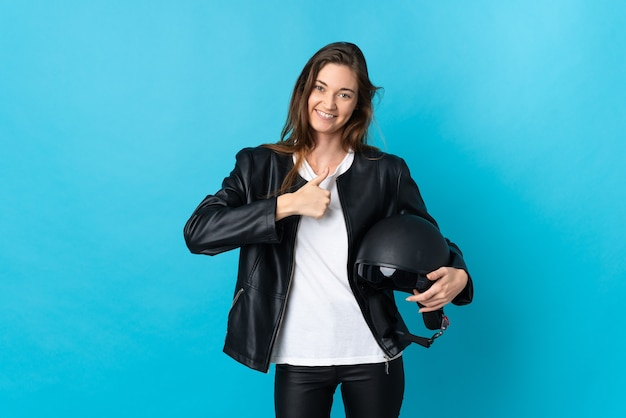 Young ireland woman holding a motorcycle helmet isolated on blue background giving a thumbs up gesture