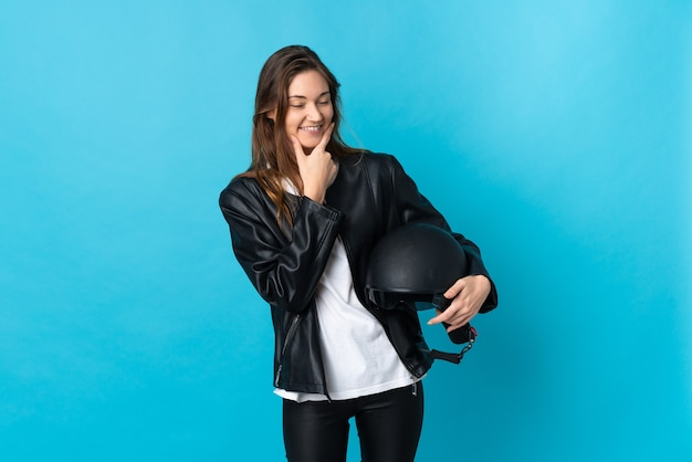 Young ireland woman holding a motorcycle helmet isolated on blue background happy and smiling