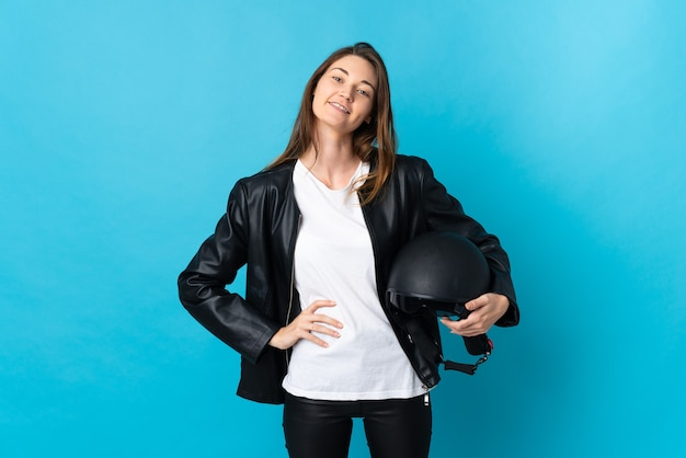 Young ireland woman holding a motorcycle helmet isolated on blue background posing with arms at hip and smiling