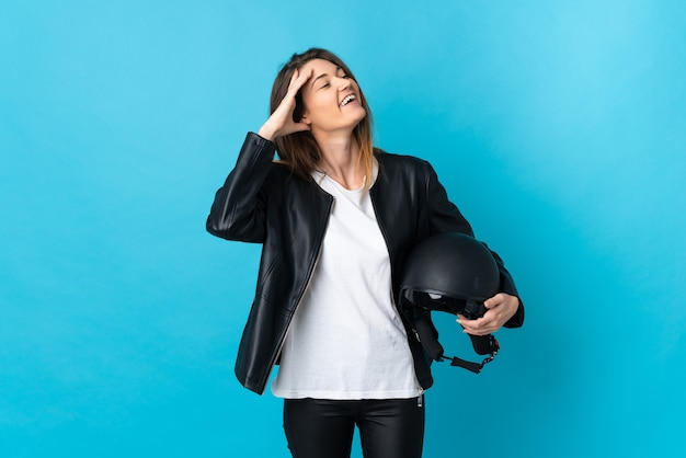 Young ireland woman holding a motorcycle helmet isolated on blue background smiling a lot