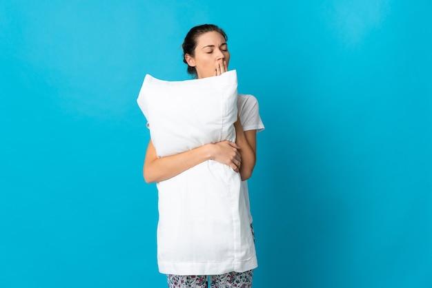 Молодая женщина ирландии изолирована на синем фоне в пижаме и держит подушку и зевая