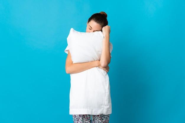 잠옷에 파란색 배경에 고립 된 젊은 아일랜드 여자는 잠자는 동안 베개를 들고