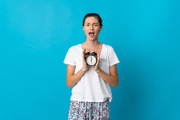 잠옷에 파란색 배경에 고립 된 젊은 아일랜드 여자와 놀란 표정으로 시계를 들고