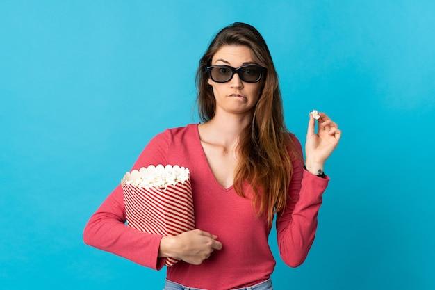 Молодая женщина из ирландии изолирована на синем фоне с 3d-очками и держит большое ведро попкорна