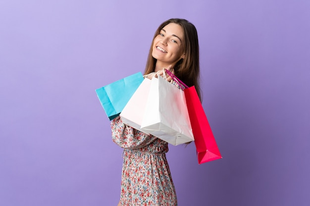 쇼핑백을 들고 웃 고 보라색 배경에 고립 된 젊은 아일랜드 여자