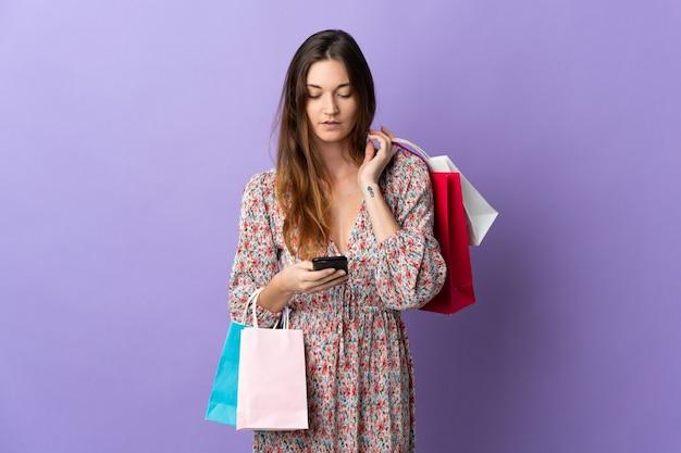 Молодая ирландская женщина изолирована на фиолетовом фоне, держа сумки для покупок и пишет сообщение со своим мобильным телефоном другу