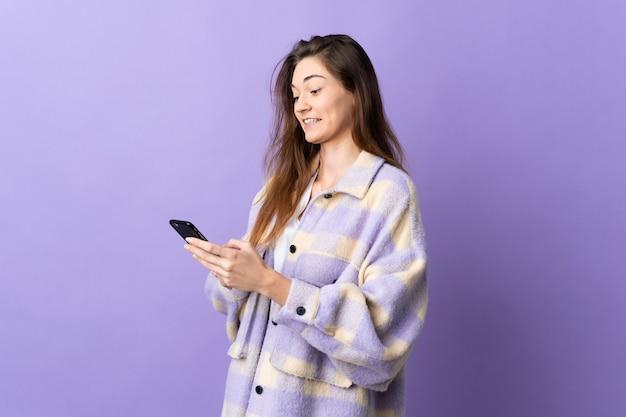 Молодая женщина ирландии изолирована на фиолетовом фоне, отправляя сообщение или электронное письмо с мобильного телефона