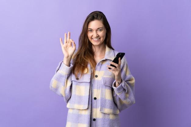 Молодая женщина ирландии изолирована на фиолетовом фоне с помощью мобильного телефона и делает знак ок