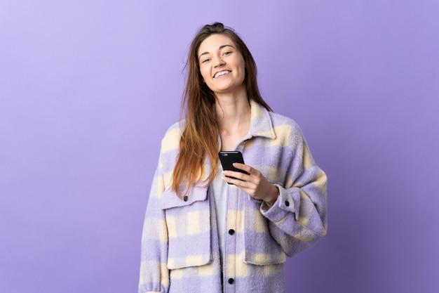 Молодая женщина ирландии изолирована на фиолетовом фоне с помощью мобильного телефона