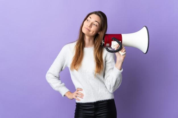 Молодая женщина из ирландии изолирована на фиолетовой стене с мегафоном и думает