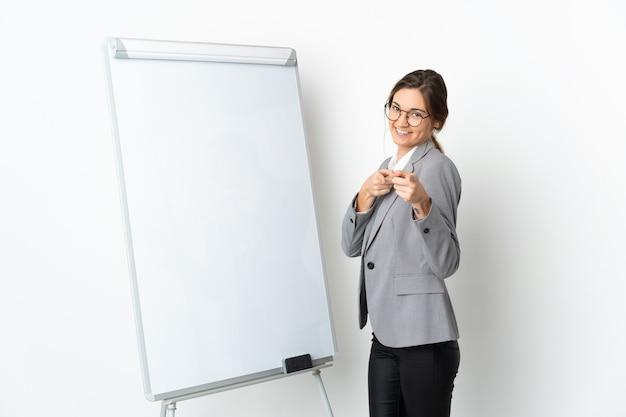 화이트 보드 및 포인트 손가락에 프레 젠 테이 션을 제공하는 흰색 배경에 고립 된 젊은 아일랜드 여자