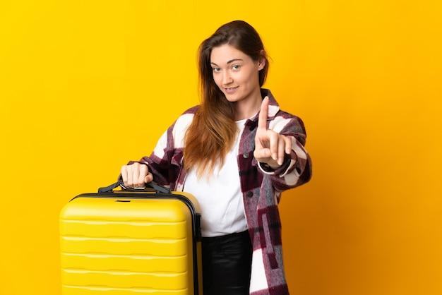 여행 가방 휴가에 노란색 배경에 고립 된 젊은 아일랜드 여자 하나를 계산