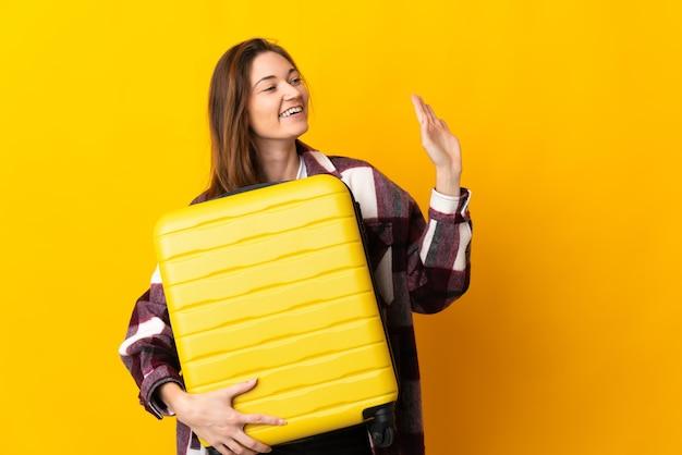 여행 가방 및 경례와 함께 휴가에 노란색 배경에 고립 된 젊은 아일랜드 여자