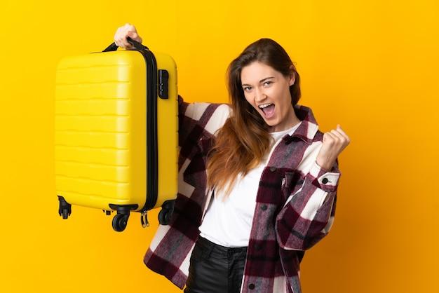여행 가방 휴가에 노란색 배경에 고립 된 젊은 아일랜드 여자