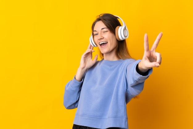 音楽を聴いて歌う黄色の背景に分離された若いアイルランドの女性