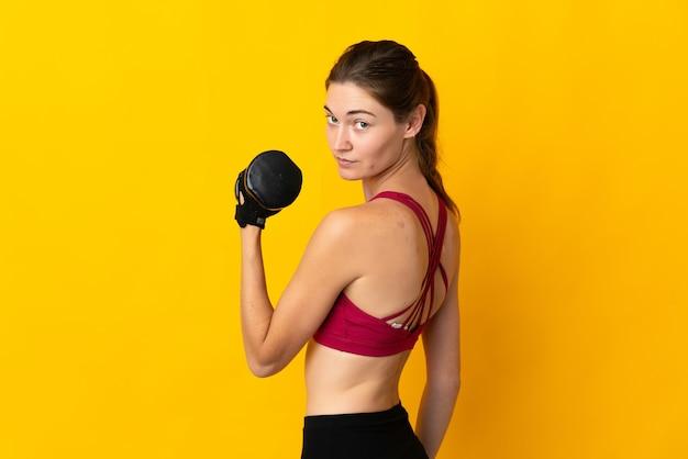 重量挙げを作る黄色の背景に分離された若いアイルランドの女性