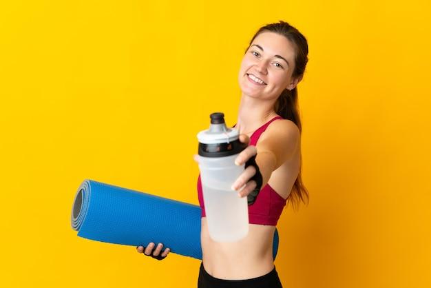 Молодая женщина ирландии изолирована на желтом фоне со спортивной бутылкой с водой и с циновкой