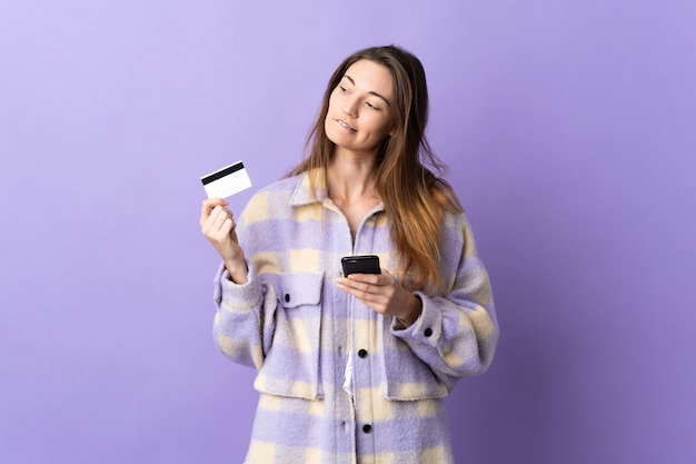 Young ireland woman isolated on purple wall buying with the mobile with a credit card while thinking