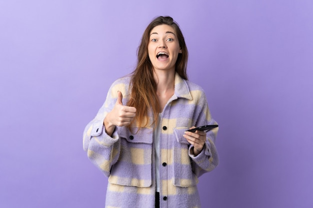 Young ireland woman isolated on purple wall using mobile phone while doing thumbs up