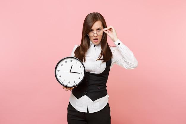 パステルピンクの背景に分離された目覚まし時計を保持している黒いスーツシャツとメガネの若いイライラした怒っているビジネス女性。女上司。達成キャリア富の概念。広告用のスペースをコピーします。
