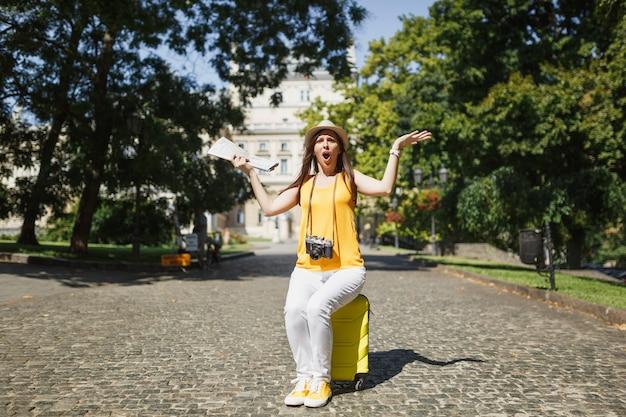 여행가방에 앉아 있는 노란 옷을 입은 젊은 화가 난 여행자 관광 여성은 야외에서 손을 펼치고 있는 도시 지도를 들고 있습니다. 주말 휴가를 여행하기 위해 해외로 여행하는 소녀. 관광 여행 라이프 스타일.